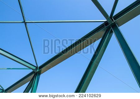 Beams of the steel bridge construction on the blue sky background,metal framework of the structure