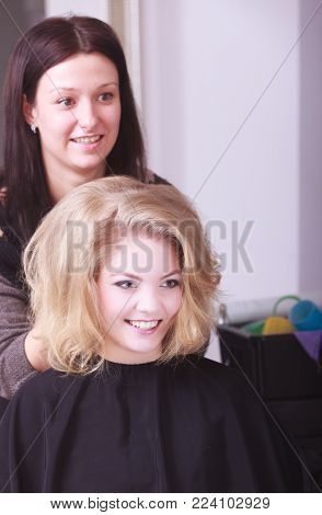 Beautiful smiling girl with blond wavy hair by hairdresser. Hairstylist combing female client young woman in hairdressing beauty salon. Hairstyle.