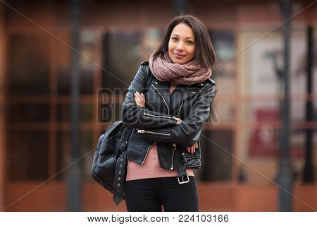Young fashion woman with backpack walking in city street. Stylish female model wearing black leather jacket and knitted scaf outdoors