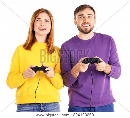 Happy couple with video game controllers on white background