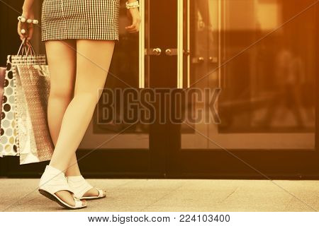 Rear view of young woman with shopping bags at the mall doorway