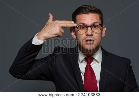 A bankrupt businessman in glasses and formal suit portrays suicide on gray background
