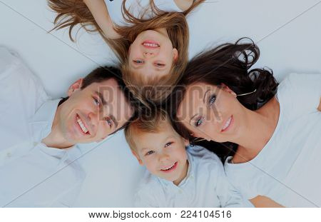Family lying down on their bed at home.