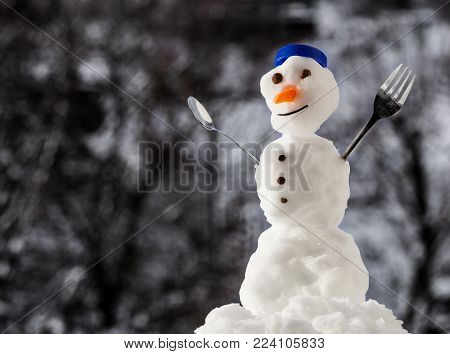 Little happy christmas snowman in blue screw top as hat red scarf with fork teaspoon outdoor. Winter season seasonal specific. Blurred background.