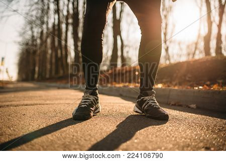 Male jogger legs, morning workout outdoors