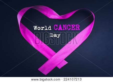 Purple ribbon forming a heart shape with World Cancer day text on black background.