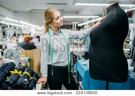 Clothes designer measures a dress on mannequin