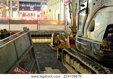 Construction site in downtown at night with excavator shovel, excavator and construction equipment
