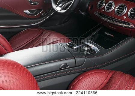 Modern Luxury car inside. Interior of prestige modern car. Comfortable leather seats. Red perforated leather cockpit. Steering wheel and dashboard. automatic gear stick shift. Car interior