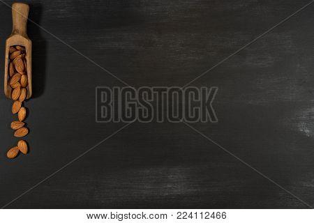 Almonds in a wooden scoop in a black chalkboard. Top view.