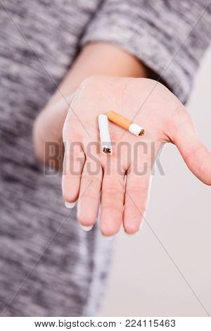 Closeup of broken cigarette on male hand. Winning with addicted nicotine problems, stop smoking. Quitting from addiction concept.