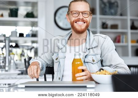 Glad Hipster Male With Long Hair And Beard, Dressed In Stylish Clothing, Browses Internet Websites,