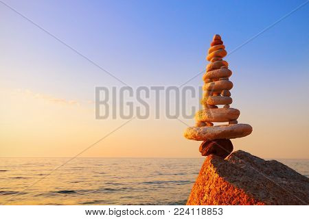 Stones balance on a background of sea sunset. Calm and meditation. Concept of harmony and balance. copy space