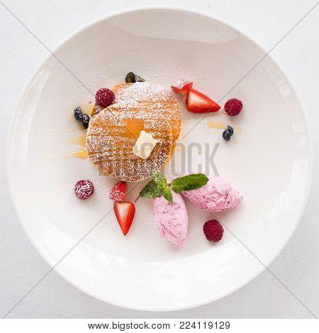 fancy restaurant breakfast dessert. Sweet fruit pancakes on white plate. Haute cuisine concept
