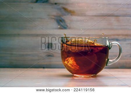 Close up transparent teacup with black tea spilling over because of added lemon