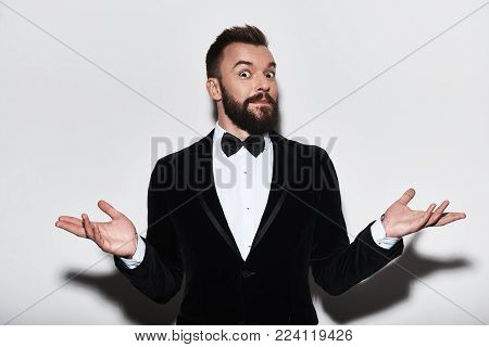Who knows? Handsome young man in full suit shrugging his shoulders while standing against grey background