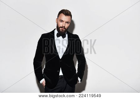 Perfect style. Handsome young man in full suit keeping hands in pockets and looking at camera while standing against grey background