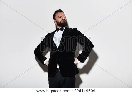 Prideful man. Handsome young man in full suit keeping hands on hips and making a face while standing against grey background