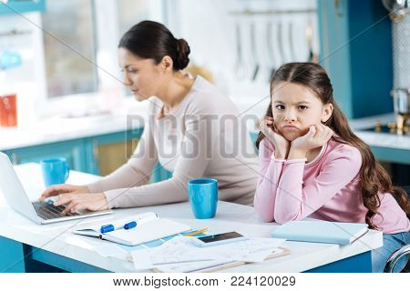 Boredom. Pretty dissatisfied dark-eyed girl holding her head with her hand and standing near her mom working on her laptop