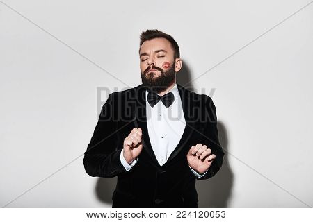 Feeling playful! Handsome young man in full suit keeping eyes closed and gesturing while standing against grey background
