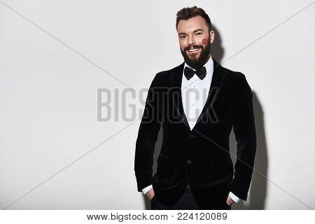 Portrait of elegance. Handsome young man in full suit keeping hands in pockets and looking at camera while standing against grey background