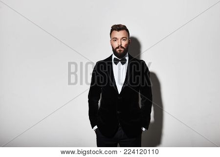 Irresistible man. Handsome young man in full suit keeping hands in pockets and looking at camera while standing against grey background