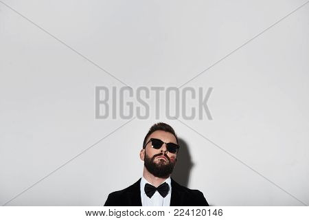 Real macho. Handsome young man in full suit and eyewear posing while standing against grey background