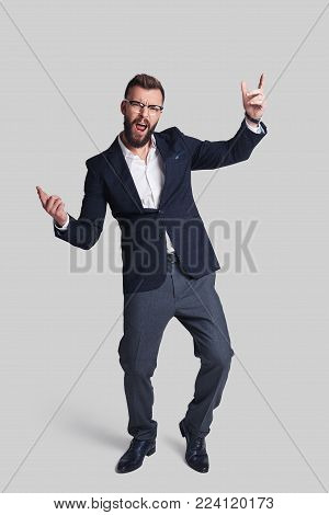 Confidence in every move. Full length of handsome young man in formalwear making a face and gesturing while standing against grey background