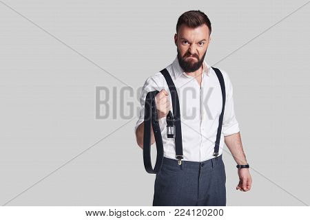 Dangerous man. Angry young man in formalwear carrying a belt and looking at camera while standing against grey background