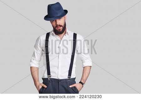 Modern gangster. Handsome young man in suspenders keeping hands in pockets and looking at camera while standing against grey background