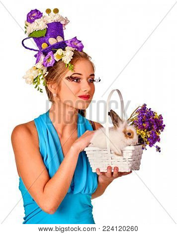 Easter girl holding bunny and eggs. Woman with holiday hairstyle and make up holding rabbit in basket with flowers. White background. Easter discounts on products for women.