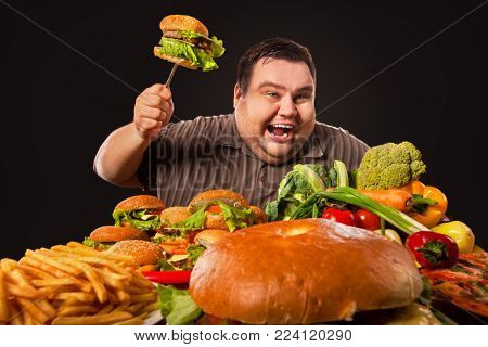 Diet fat man with good appetite who makes choice between healthy and unhealthy food. Overweight mad male with hamburgers, french fries trying to lose weight first time on black background.