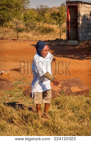 African child playing in the yard in the village, pit latrine in the back, Botswana