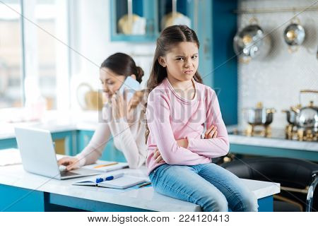 Unhappy. Pretty miffed dark-eyed girl holding her arms crossed and sitting near her mom working on her laptop