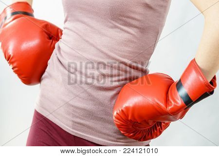 Unrecognizable sporty woman wearing red boxing gloves. Studio shot on dark background.