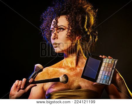 Woman with decorative cosmetics. Girl with curls holds eye shadow and brush on dark background. Portrait of golden powder on female bare shoulders. Professional make-up artist. Spring make-up.