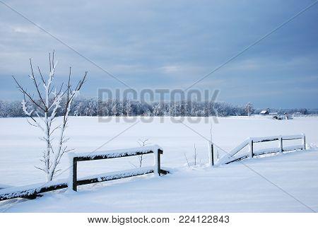 Broken wooden fence in a wintry landscape