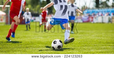 Soccer Football Kick. Young Player Kicking Soccer Ball. Footballers Running the Ball
