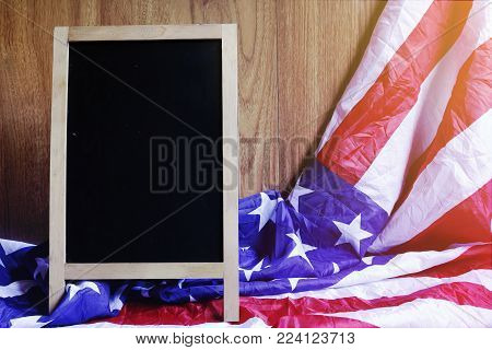 Chalkboard and USA Flag on Brown Wooden Wall America Flag Background with Copy Space for MLK Day, President's Day, Patriot Day, 4th of July, Independence Day.