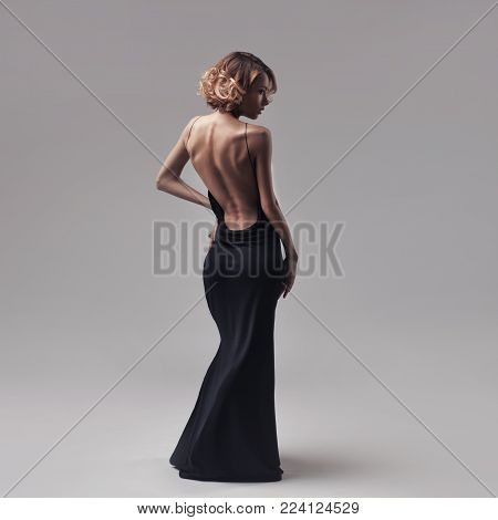 beautiful blond woman model with curly hair posing in elegant black dress on the grey studio background