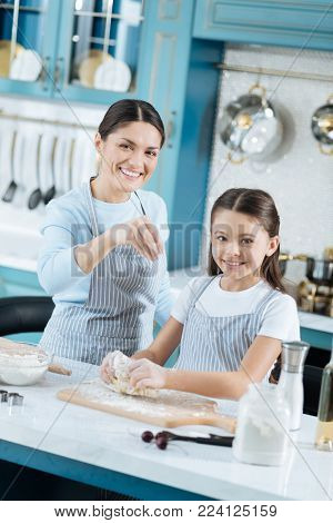 Baking with joy. Pretty content dark-haired schoolgirl and mother smiling and making some dough for cookies while wearing pinafores