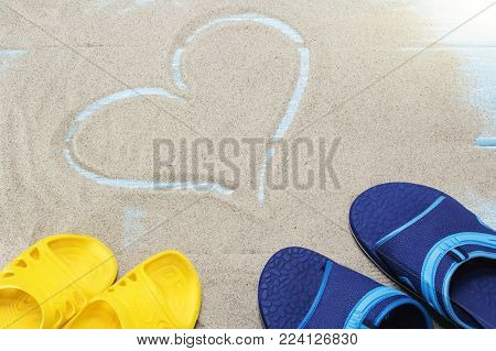 blue, yellow flip flops and heart on sandy beach