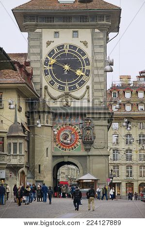 BERN, SWITZERLAND - FEBRUARY 23, 2012: Unidentified people walk by the street with the historic Bern Clock tower at the background in Bern, Switzerland.