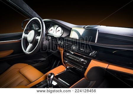 Modern luxury car Interior - steering wheel, shift lever and dashboard. Car interior luxury inside. Steering wheel, dashboard, speedometer, display. Red and black leather cockpit