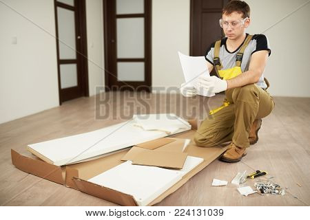 Worker install furniture with instruction. Repair works in flat. Professional help with installation furniture.