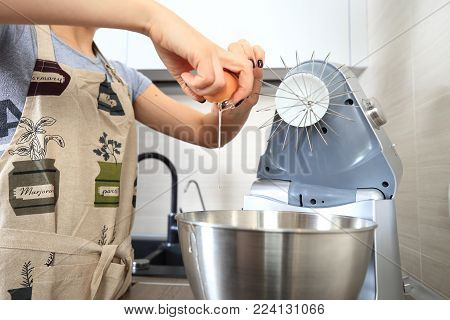 Woman cooking cake. Housewife adds egg in bowl of food processor.