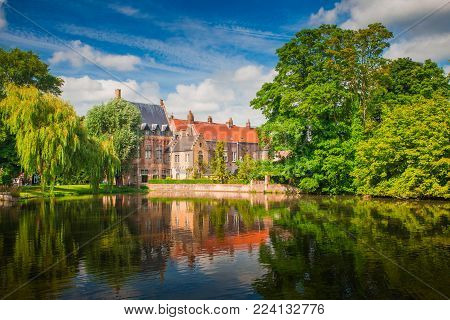 Brugge sunny cityscape. Old buildings of Bruges and green trees reflected in lake. Historical center of Europe.