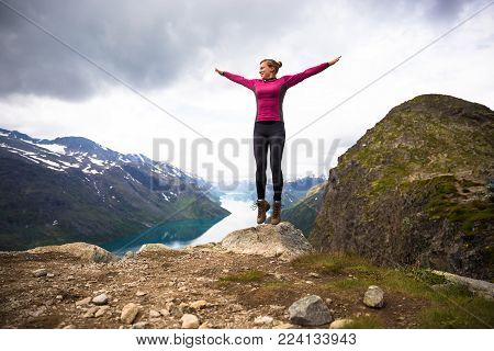 Sport woman hiking on Besseggen. Hiker enjoy beautiful lake and good weather in Norway