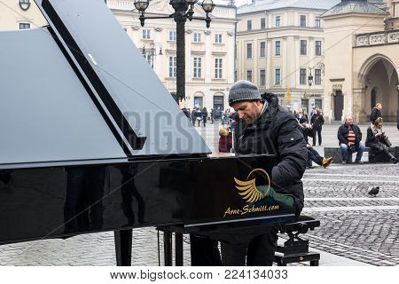KRAKOW, POLAND, January 27, 2017  A street musician Arne Schmitt plays the piano on the main Rynok square in Krakow