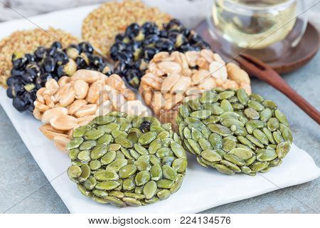 Korean traditional sweet snacks with peanuts, pumpkin seeds, black soybeans and chinese buckwheat on a white plate, horizontal